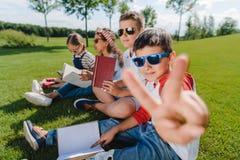 在太阳镜打手势在照相机的阅读书和一个男孩的孩子 免版税库存照片