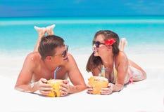 在太阳镜的夫妇用在热带海滩的椰子汁 免版税库存图片