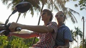 在太阳镜的年轻时兴的夫妇在驾驶通过太阳的摩托车的热带海岛附近移动 慢 股票录像