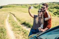 在太阳镜的微笑的时髦的夫妇有采取在智能手机的咖啡杯的selfie在农村的汽车附近 库存图片