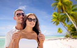 在太阳镜的愉快的夫妇在热带海滩 图库摄影