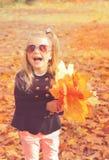 在太阳镜的愉快的快乐的白肤金发的小女孩画象,拿着与黄色槭树叶子的花束 免版税库存照片