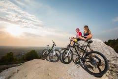 在太阳镜的愉快的骑自行车者夫妇坐岩石 库存照片