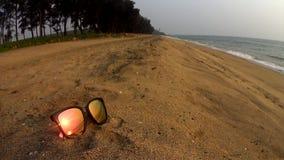 在太阳镜的日落反射在sandbeach的海滩 股票视频