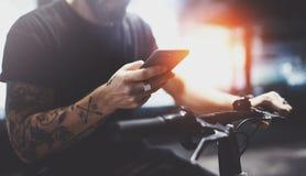 在太阳镜的有胡子的被刺字的男性使用在乘坐的智能手机乘电滑行车以后在城市 免版税库存照片