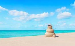 在太阳镜的正面含沙雪人在晴朗的热带海洋海滩 免版税库存图片