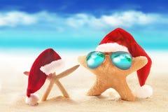 在太阳镜的海星在夏天海滩和圣诞老人帽子 免版税库存照片