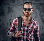 在太阳镜的红头发人有胡子的男性有在他的肩膀的一个袋子的 库存图片