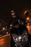 在太阳镜的美丽的少妇骑马摩托车通过城市街道在晚上 图库摄影