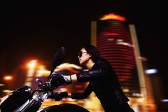 在太阳镜的美丽的少妇骑马摩托车通过城市街道在晚上 免版税库存照片