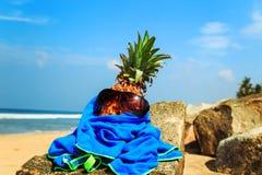 在太阳镜的菠萝在海滩 库存图片
