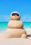 在太阳镜的滑稽的含沙雪人在热带晴朗的海洋海滩 免版税库存图片
