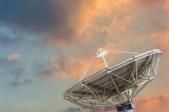 在太阳集合背景的卫星盘 免版税库存照片