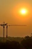 在太阳sujuct blure下的建筑用起重机剪影 库存图片