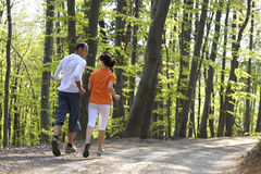 在夫妇森林跑步的视图之后 免版税库存图片