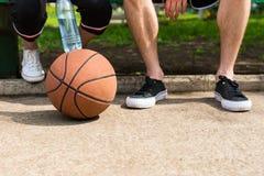 在夫妇的脚的篮球坐公园长椅 免版税库存照片