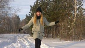 在夹克步行和跃迁打扮的年轻美丽的白种人女孩妇女使用在冬天森林里在多雪的天 股票视频