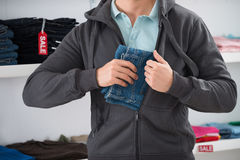 在夹克的人掩藏的牛仔裤在商店 免版税库存照片