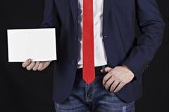 在夹克的商人在他的手上的拿着一个空白纸 图库摄影