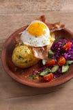 在夹克的被烘烤的土豆用乳酪装载了并且冠上了与烟肉和煎蛋在板材有菜的 库存图片