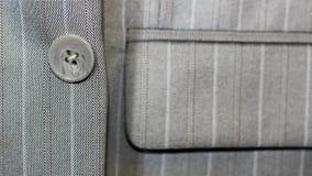 在夹克,特写镜头,灰色企业精神衣服的一个按钮 图库摄影