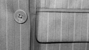 在夹克,特写镜头,灰色企业精神衣服的一个按钮 库存图片