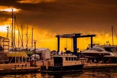在奇怪的天气的小游艇船坞日落 库存图片