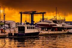 在奇怪的天气的小游艇船坞日落 库存照片