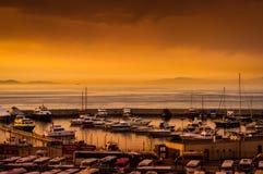 在奇怪的天气的小游艇船坞日落 图库摄影