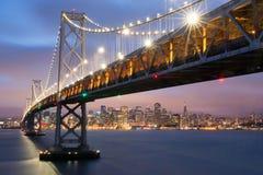 在奥克兰圣弗朗西斯科海湾桥梁和旧金山地平线,加利福尼亚的黄昏 图库摄影