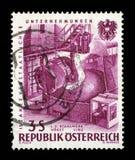 在奥地利打印的邮票,致力于国有化的产业第15周年,代表了倾吐的钢, VOEST,林茨 免版税库存图片