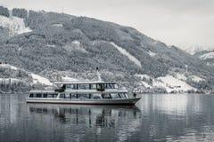 在奥地利滨湖采尔冻湖的有雪的和美丽的山的旅游巡航在背景 旅游船小船s 免版税库存照片