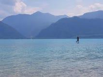 在奥地利站立一个清楚的蓝色moutain湖的桨手 免版税库存图片
