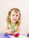 在女孩之后铸造彩色塑泥 免版税库存图片