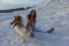 在女孩前面的大牧羊犬狗坐白色岩石,棉花堡 免版税库存照片