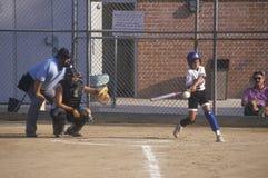 在女孩垒球赛的女孩摇摆的棒在布伦特伍德,加州 免版税库存照片