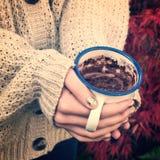 在女孩手上的特写镜头有拿着热巧克力的毛线衣的 免版税图库摄影