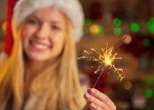 在女孩的特写镜头拿着闪烁发光物的圣诞老人帽子的 图库摄影