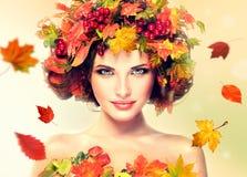 在女孩的红色和黄色秋叶朝向 库存图片