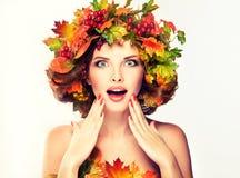在女孩的红色和黄色秋叶朝向 库存照片