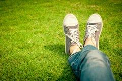 在女孩腿的青年运动鞋在草 免版税库存图片