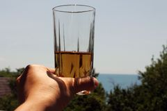 在女孩苹果汁的手上在玻璃的 在天空的背景 免版税库存图片
