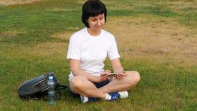 在女孩附近的慢动作照相机坐绿草在公园 工作在互联网上的创造性的女商人 影视素材