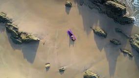 在女孩附近的行动在沙子海滩鸟瞰图中的席子的 股票录像