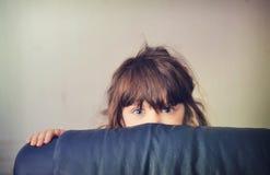 在女孩隐藏之后演奏寻求沙发的一点 库存照片