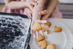 在女孩` s手上的心形的曲奇饼 免版税库存图片