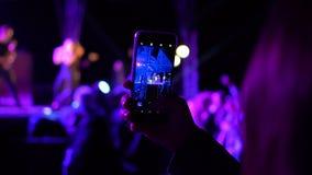 在女孩` s手智能手机射击和跳舞在岩石和迪斯科生活夏天节日音乐会,人人群  影视素材