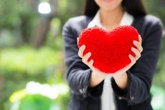 在女实业家手亚裔妇女的红色心脏有希望概念的 库存照片