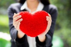 在女实业家手亚裔妇女的红色心脏有希望概念的 库存图片