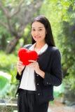 在女实业家手亚裔妇女的红色心脏有希望概念的 图库摄影
